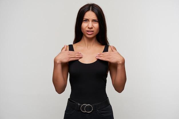 Niezadowolona młoda, długowłosa brunetka kobieta trzymająca dłonie na piersi z dąsaniem, marszcząca brwi podczas pozowania na biało