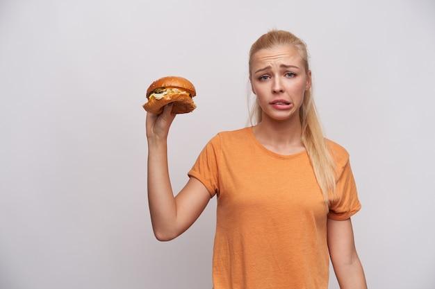 Niezadowolona młoda, dość długowłosa blondynka z fryzurą w kucyk marszczy brwi i dąsa się, trzymając niezdrowe jedzenie w uniesionej ręce, stojąc na białym tle