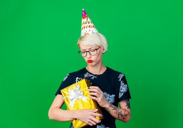 Niezadowolona młoda dziewczyna blondynka w okularach i czapce urodzinowej, trzymając i patrząc na pudełko na białym tle na zielonym tle z miejsca na kopię