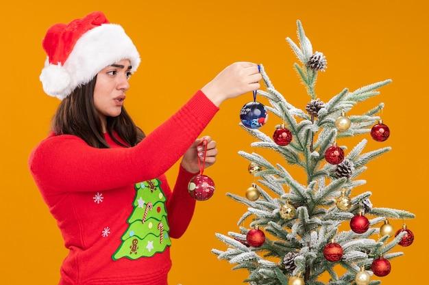 Niezadowolona młoda dziewczyna rasy kaukaskiej w czapce świętego mikołaja dekorująca choinkę szklanymi kulkami