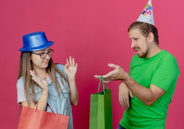 Niezadowolona młoda dziewczyna w niebieskim kapeluszu imprezowym trzyma czerwoną torbę z prezentami i podnosi ręce, nie patrząc na niepewnego młodego mężczyznę w kapeluszu imprezowym i trzymającego zieloną torbę z prezentami na różowej ścianie