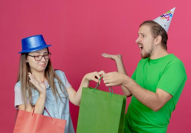 Niezadowolona młoda dziewczyna w niebieskim kapeluszu imprezowym trzyma czerwoną torbę z prezentami i podnosi rękę, biorąc zieloną torbę z prezentami od zirytowanego młodego mężczyzny w kapeluszu imprezowym na różowej ścianie