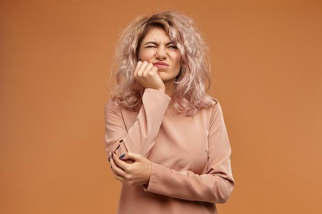 Niezadowolona młoda europejka z luźną, niechlujną fryzurą ze znudzonym lub sfrustrowanym wyrazem twarzy, krzywiąca się z bólu, trzymająca dłoń na policzku