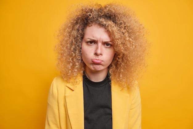 Niezadowolona młoda europejka z naturalnymi jasnymi kręconymi włosami w torebkach usta czuje się sfrustrowana rozczarowaniem czymś sprawia, że nieszczęśliwy, obrażony grymas ma na sobie żółty strój formalny stoi w pomieszczeniu