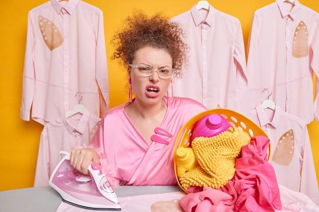 Niezadowolona młoda gospodyni uśmiecha się ze zmęczoną i zirytowaną miną, nosi okulary i szlafrok, chodząc do prasowania, wyprane pranie ma dużo pracy w domu. zmęczony obowiązkami domowymi.