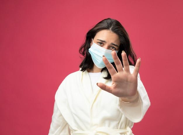Niezadowolona młoda kaukaska chora dziewczyna ubrana w szatę i maskę patrząc na kamerę wyciągającą rękę w kierunku kamery, gestykulując bez izolacji na szkarłatnym tle z przestrzenią do kopiowania