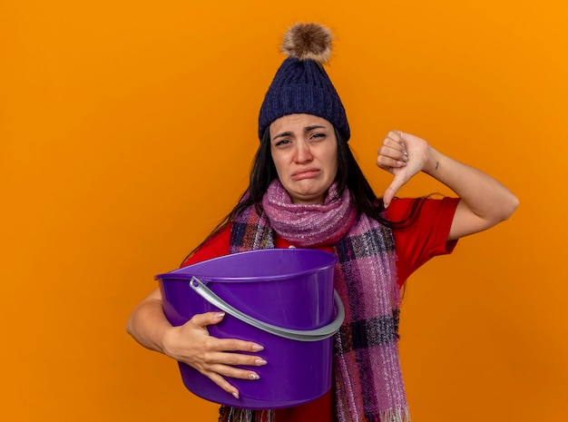 Niezadowolona młoda kaukaska chora dziewczyna w czapce zimowej i szaliku trzymająca plastikowe wiadro mdłości patrząc na kamerę pokazująca kciuk w dół na białym tle na pomarańczowym tle z miejscem na kopię