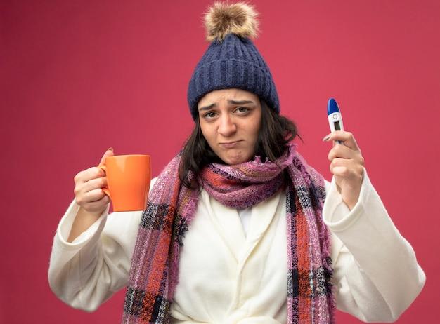 Niezadowolona młoda kaukaska chora dziewczyna w czapce zimowej szaty i szaliku trzymająca filiżankę herbaty i termometr patrząc na kamerę odizolowaną na szkarłatnym tle