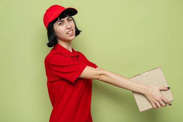 Niezadowolona młoda kaukaska dziewczyna dostawcza stojąca bokiem, trzymająca kartonowe pudełko
