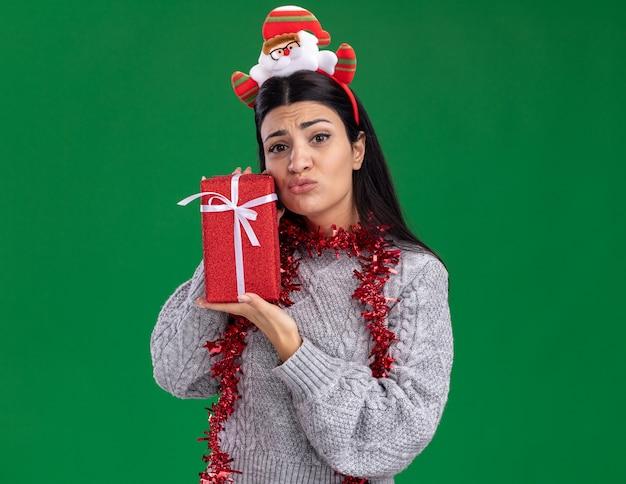 Niezadowolona młoda kaukaska dziewczyna ubrana w opaskę świętego mikołaja i świecącą girlandę na szyi, trzymając pakiet prezentów patrząc na kamerę z zaciśniętymi ustami odizolowanymi na zielonym tle z miejscem na kopię