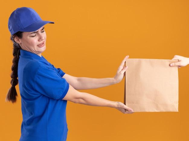 Niezadowolona młoda kobieta dostarczająca w mundurze i czapce
