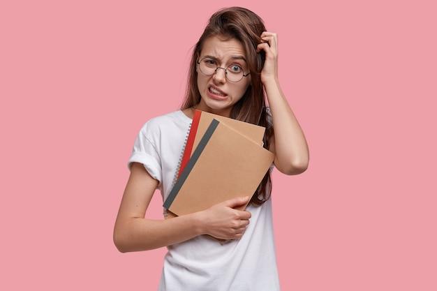 Niezadowolona młoda kobieta drapie się po głowie, zaciska zęby, patrzy oszołomiona, myśli o kreatywnych pomysłach na napisanie eseju, trzyma notesy