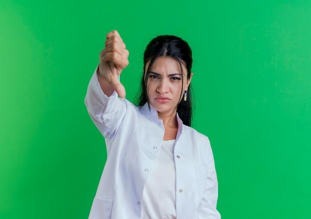 Niezadowolona młoda kobieta lekarz ubrana w szlafrok medyczny pokazujący kciuk w dół na białym tle na zielonej ścianie z miejsca na kopię