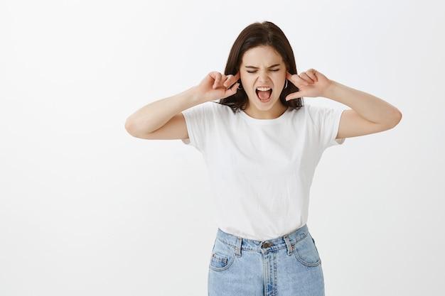 Niezadowolona młoda kobieta pozuje na białej ścianie