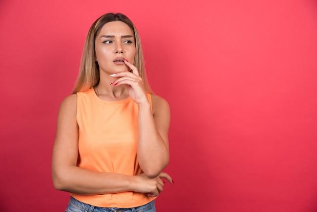 Niezadowolona młoda kobieta trzymająca rękę na brodzie na czerwonej ścianie.