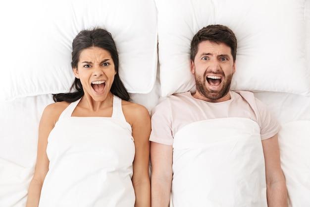 Niezadowolona młoda, kochająca się para leży w łóżku pod kocem krzycząc