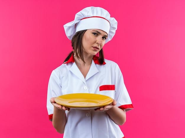 Niezadowolona młoda kucharka ubrana w mundur szefa kuchni trzymająca talerz odizolowany na różowej ścianie