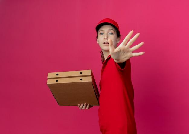 """Niezadowolona młoda ładna dostawa dziewczyna w czerwonym mundurze i czapce stojącej w widoku profilu, trzymająca paczki z pizzą i wyciągając rękę, gestem """"nie"""""""