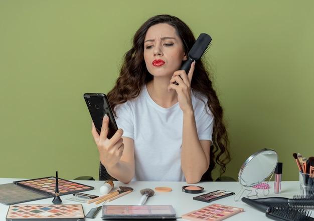 Niezadowolona młoda ładna dziewczyna siedzi przy stole do makijażu z narzędziami do makijażu, trzymając i patrząc na telefon komórkowy i trzymając grzebień w pobliżu ucha izolowanego na oliwkowym tle