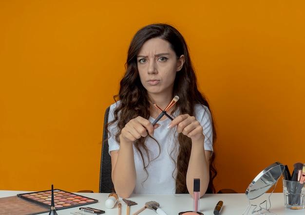 Niezadowolona młoda ładna dziewczyna siedzi przy stole do makijażu z narzędziami do makijażu, trzymając pędzle do makijażu i gestykulując przed kamerą na białym tle na pomarańczowym tle