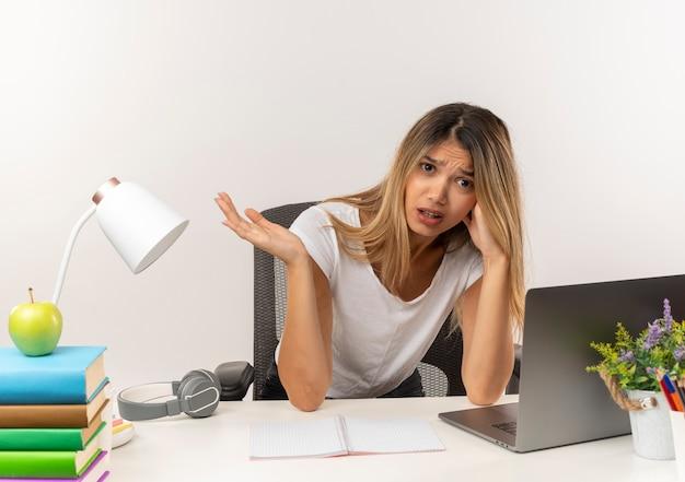 Niezadowolona młoda ładna dziewczyna studentka siedzi przy biurku z narzędziami szkolnymi, kładąc rękę na głowie i pokazując pustą dłoń na białym tle