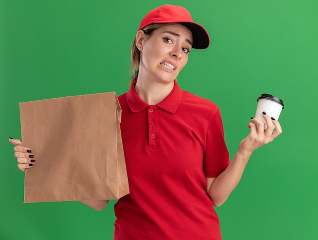 Niezadowolona młoda ładna dziewczyna w mundurze dostawy trzyma papierowy pakiet i papierowy kubek na zielono