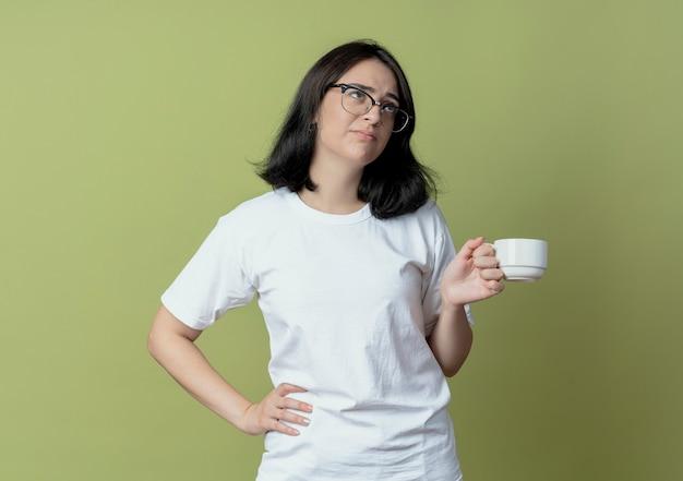 Niezadowolona młoda ładna dziewczynka kaukaski w okularach patrząc w górę kładąc rękę na talii trzymając kubek na białym tle na oliwkowym tle z miejsca na kopię