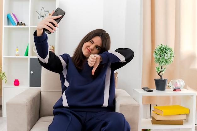 Niezadowolona młoda, ładna kaukaska dziewczyna siedzi na fotelu w zaprojektowanym salonie, pokazując kciuk w dół, mrugając i robiąc selfie