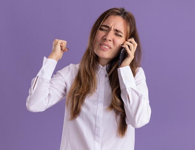 Niezadowolona młoda ładna kaukaska dziewczyna trzyma pięść i rozmawia przez telefon
