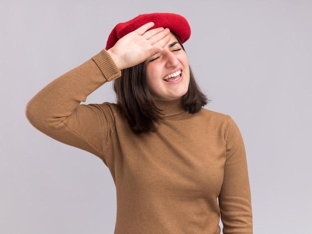 Niezadowolona młoda ładna kaukaska dziewczyna w berecie kładzie rękę na czole