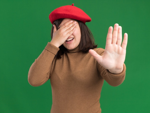Niezadowolona młoda ładna kaukaska dziewczyna w berecie zakrywa twarz i gestykuluje znak stopu
