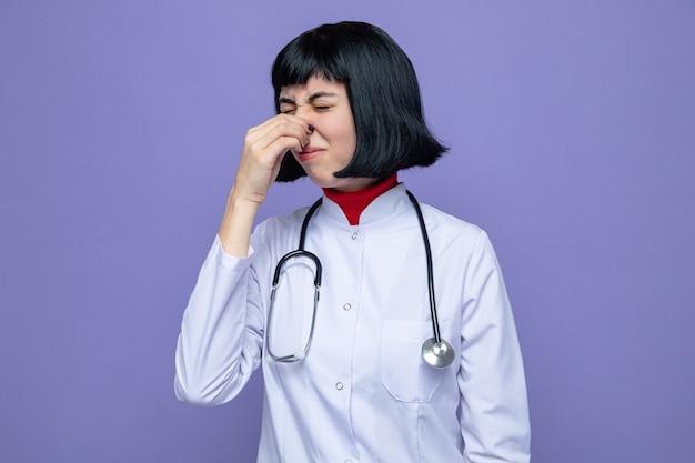 Niezadowolona młoda ładna kaukaska kobieta w mundurze lekarza ze stetoskopem trzymającym nos