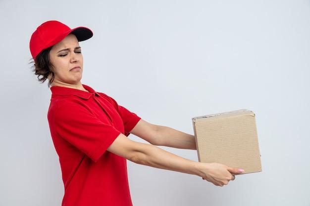 Niezadowolona młoda ładna kobieta dostawy trzymająca kartonowe pudełko