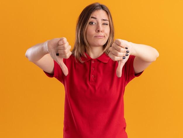 Niezadowolona młoda ładna kobieta kciuki w dół z dwiema rękami odizolowanymi na pomarańczowej ścianie