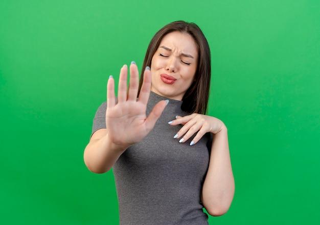 Niezadowolona młoda ładna kobieta trzyma rękę na klatce piersiowej i gestykuluje, zatrzymując się przy aparacie z zamkniętymi oczami na białym tle na zielonym tle z miejsca na kopię