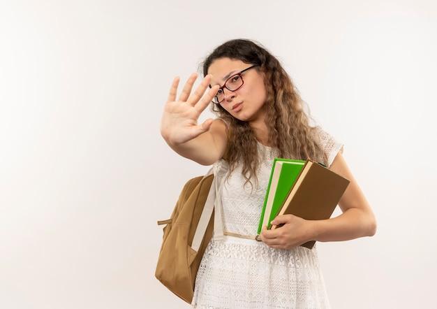 Niezadowolona młoda ładna uczennica w okularach i plecak trzymając książki robi gest stopu w aparacie na białym tle na białym tle z miejsca kopiowania