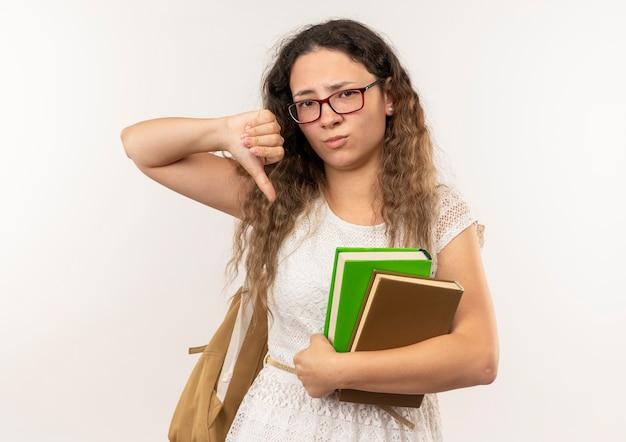 Niezadowolona młoda ładna uczennica w okularach iz powrotem trzyma książki pokazując kciuk w dół na białym tle