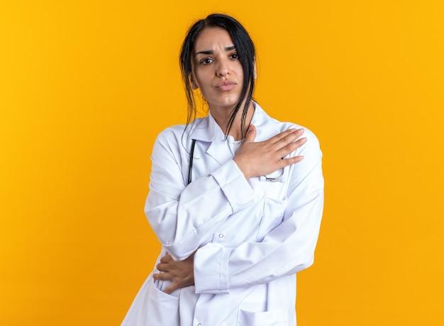 Niezadowolona młoda lekarka ubrana w szatę medyczną ze stetoskopem, kładąc ręce na sobie na białym tle na żółtym tle
