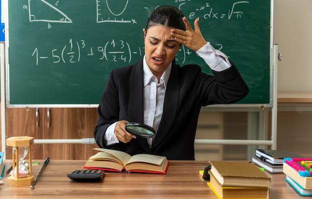 Niezadowolona młoda nauczycielka siedzi przy stole z przyborami szkolnymi, czytając książkę z lupą, kładąc rękę na czole w klasie