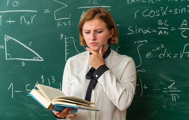 Niezadowolona młoda nauczycielka stojąca przed tablicą czytająca książkę chwyciła podbródek w klasie