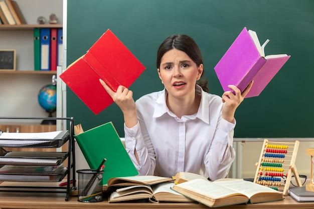 Niezadowolona młoda nauczycielka trzyma książkę siedzącą przy stole z narzędziami szkolnymi w klasie