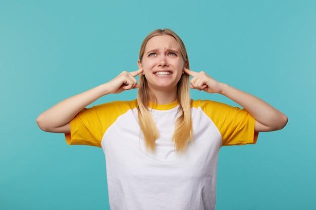 Niezadowolona młoda niebieskooka jasnowłosa kobieta wkładająca palce wskazujące do uszu, próbująca uniknąć głośnych dźwięków i krzywiąca się niezadowolona z twarzy, odizolowanej na niebieskim tle