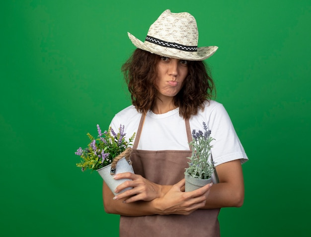 Niezadowolona młoda ogrodniczka w mundurze, ubrana w kapelusz ogrodniczy, trzymająca i krzyżująca kwiaty w doniczkach
