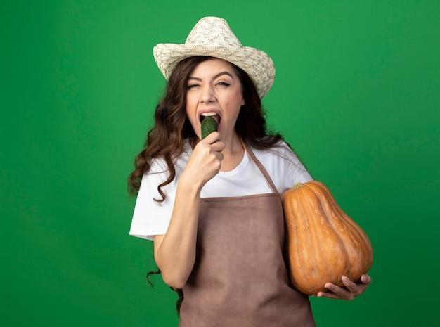 Niezadowolona młoda ogrodniczka w mundurze w kapeluszu ogrodniczym trzyma dynię i gryzie ogórka na zielonej ścianie z miejscem na kopię