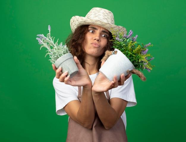 Niezadowolona młoda ogrodniczka w mundurze w kapeluszu ogrodniczym, trzymając i patrząc na kwiaty w doniczkach