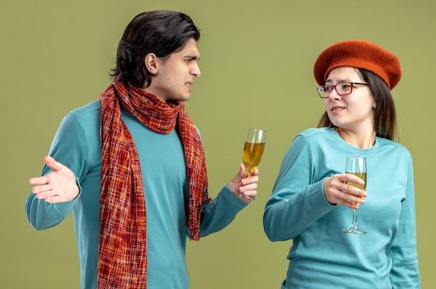 Niezadowolona młoda para na walentynki facet ubrany w szalik dziewczyna w kapeluszu trzymająca kieliszek szampana, patrząc na siebie na białym tle na oliwkowym tle
