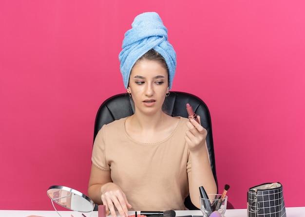 Niezadowolona młoda piękna dziewczyna siedzi przy stole z narzędziami do makijażu owiniętymi włosami w ręcznik, trzymając i patrząc na szminkę na białym tle na różowym tle