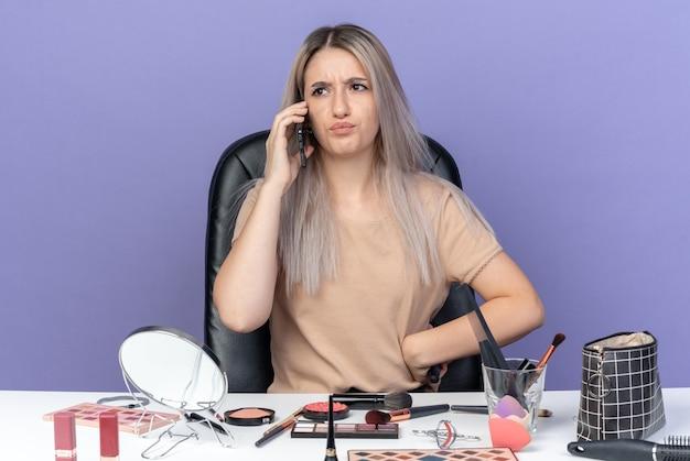 Niezadowolona młoda piękna dziewczyna siedzi przy stole z narzędziami do makijażu, rozmawia przez telefon, trzymając grzebień, kładąc rękę na biodrze na białym tle na niebieskim tle
