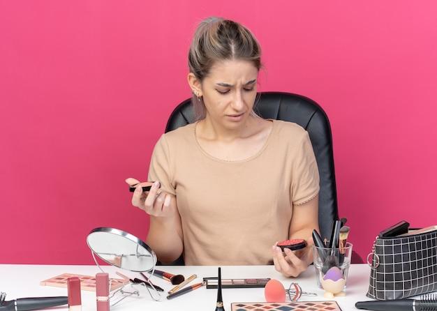 Niezadowolona młoda piękna dziewczyna siedzi przy stole z narzędziami do makijażu, trzymając i patrząc na rumieniec w proszku na białym tle na różowym tle