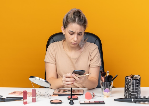 Niezadowolona młoda piękna dziewczyna siedzi przy stole z narzędziami do makijażu, trzymając pędzel do makijażu i patrząc na telefon w dłoni na białym tle na pomarańczowym tle